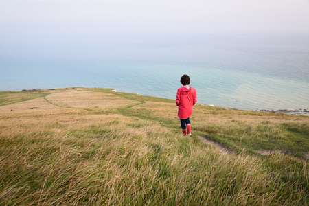 Girl walking down to the cliff in green England countryside, Beachy Head, Eastbourne Banque d'images - 101844147