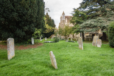 Small cemetery with green grass, with a church in the background. Banque d'images - 101817611