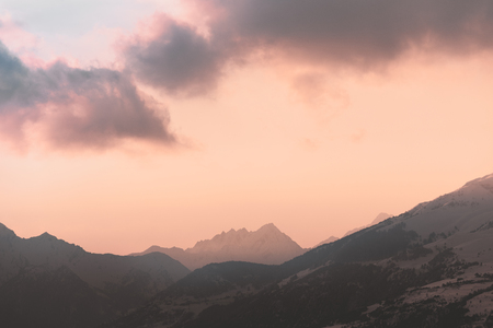 Sunset with red cloud over distant mountain peaks, blue, yellow, orange, mellow