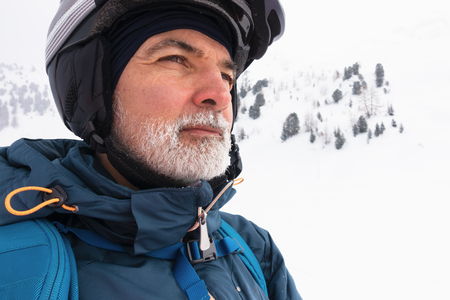 Old man with white frozen beard on snowy mountain with ski googles and helmet, portrait, watching at distance, cold winter weather.
