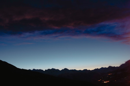 Blue hour on mountain range in the distance with red purple clouds and distant lights from villages Banco de Imagens