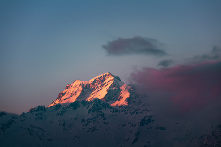 Mountain peak at sunset with golden yellow color and red clouds on sunset, sunrise, snow.