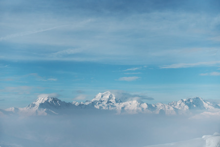 Snowy mountain range in a distance, with clouds above and under the tops, fog with a blue sky Banco de Imagens