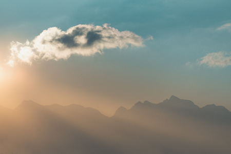 Mountain peaks and cloud on a sunny day, with golden sun rays passing through