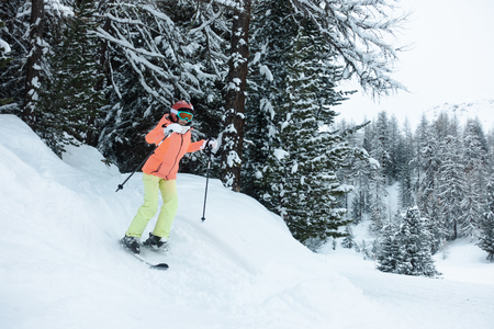 Young woman, girl in orange, green, yellow ski suit skiing in the forest