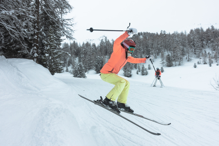 Young woman, girl in orange, green, yellow ski suit jumping in the forest