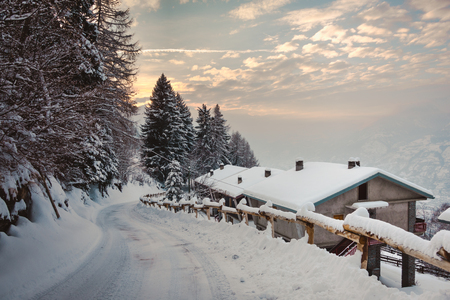 Mountain houses and road covered with snow going to the sun, yellow wooden fence, pine trees, blue sky and rising sun