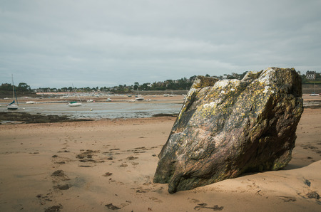 Big rock in Brittany beach, revealed at the low tide with boats laying on the bottom of the sea in the distance, France