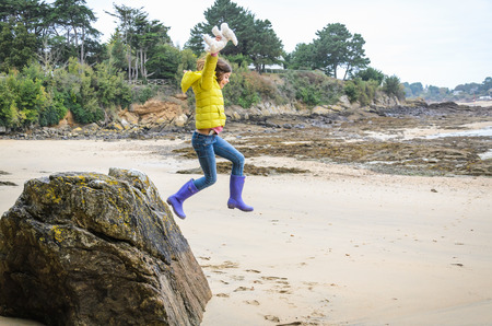 Little girl jumping from the big rock on the beach, trees and bushes in the distance, France, Normandy