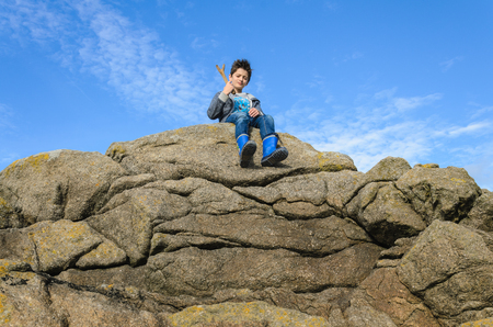 Boy in a blue dress with a wooden toy sits on top of a cliff , big rock with a layers,  on the beach, focus on the child