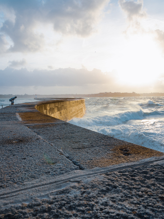 Big waves crushing on curved stone pier, on stormy weather with vivid sunset, big tide, Saint Malo, France.