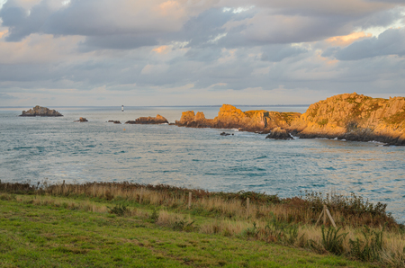 Cliffs with lighthouse in the distance, with rocks illuminated by sun rays just before sunset, Brittany, France Banco de Imagens