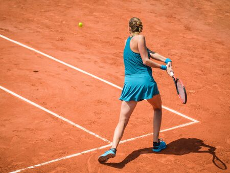 Back view  of a woman playing backhand in tennis outdoor competition game