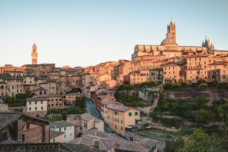 Cityscape of Siena, a beautiful medieval town in Tuscany, with view of the Dome Bell Tower of Siena Cathedral (Duomo di Siena), landmark Mangia Tower and Basilica of San Domenico, Italy Banco de Imagens