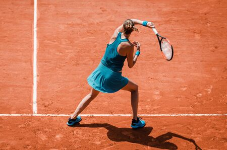 Back view  of a woman playing forehand in tennis outdoor competition game