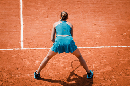 Back view  of a woman playing tennis, waiting to receive service,  outdoor competition game, running, professional