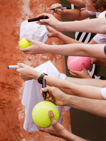 Tennis fans extending arms to get signature from player Editorial