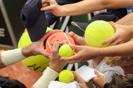 Tennis player signs autograph on a tennis ball after win, closeup photo showing tennis balls and hands of tennis fans, man making signature. Stock Photo - 124912097