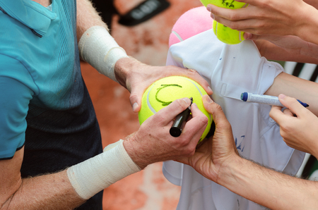 Tennis player signs autograph on a tennis ball after win, closeup photo showing tennis balls and hands of tennis fans, man making signature. Editorial