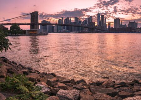 Brooklyn Bridge and rocks at the beach at sunset viewed from Brooklyn Bridge park