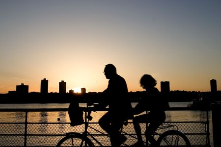 Two cyclists on the tandem bike riding along Hudson River