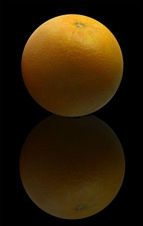 Fresh juicy orange on the black background with reflection.