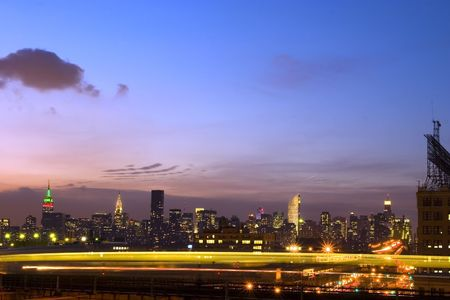 New York city Skyline at dusk with motion blur of moving train.