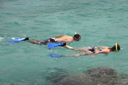 Yong couple snorkeling in the emerald water near Rivera Maya shore