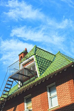 Green roof with Mediterranean tiles against blue sky