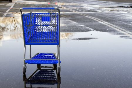 Lonely shopping cart on the empty parking lot with reflection.