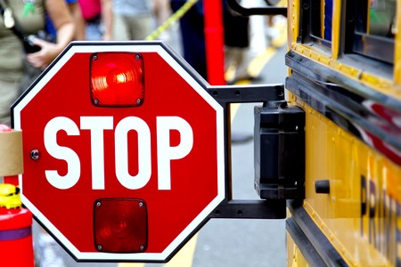 school bus: Stop sign with the flashing red light on the school bus.
