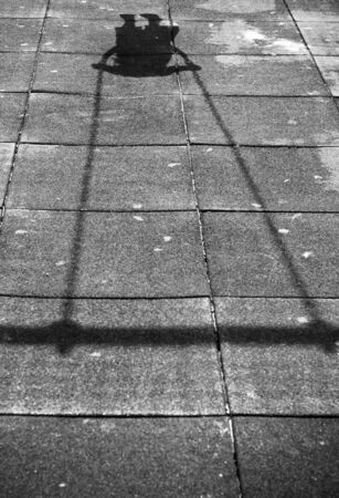 Shadow of the little girl on the swing. Black and White.