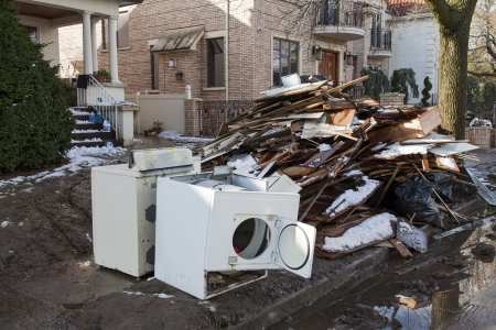 the aftermath: NEW YORK - NOVEMBER 8, 2012:Pile of garbage, debris and household items near flooded and damaged house after Hurricane Sandy  on Manhattan Beach on November 8, 2012, Brooklyn, NY Editorial