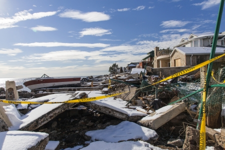 NEW YORK - 8. November 2012: Stapel von Schutt und Boot in der Nähe überflutet und beschädigten Häuser nach dem Hurrikan Sandy am Manhattan Beach am 8. November 2012, Brooklyn, NY Editorial
