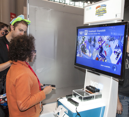 NEW YORK - October 13  Fan tries new game  from Wii during Comic Con 2013 at The Jacob K  Javits Convention Center on October 13, 2013 in New York City  Stock Photo - 22771614