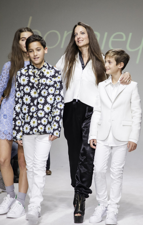 cahill: New York, NY, USA - October 19, 2014: Designer Bonnie Young on the runway with Celia Babini, Kyah Cahill and Brando Babini on the runway during the Bonnie Young preview at petitePARADEKids Fashion Week at the Bathhouse Studios, Manhattan