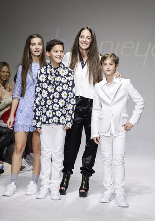 cahill: New York, NY, USA - October 19, 2014: Designer Bonnie Young poses with Celia Babini, Kyah Cahill and Brando Babini on the runway during the Bonnie Young preview at petitePARADEKids Fashion Week at Bathhouse Studios, Manhattan Editorial