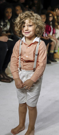 badhuis: New York, NY, USA - 19 oktober 2014: Een model loopt de baan tijdens de Charm voorvertoning bij petitePARADE  Kids Fashion Week in Badhuis Studios, Manhattan