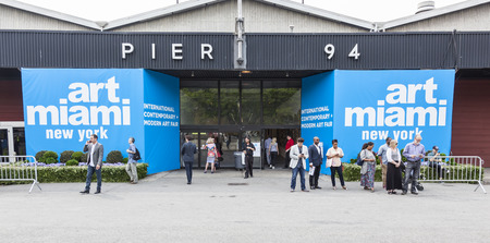 modern art: New York, NY, USA - May 16, 2015: Visitors at entrance of Art Miami New York, the international contemporary and modern art fair at Pier 94, Manhattan. Paintings, sculpture, installation from about 1200 artists from over 50 countries presented by 100 lead Editorial
