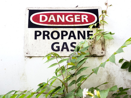 """propane gas: Dirty 'Danger"""" sign on propane gas tank in rural area"""