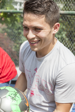 red bull: New York, NY, USA - May 26, 2016: New York Red Bull player Alex Muyl celebrates Red Nose Day with kids at the school yard of PS 154, Brooklyn Editorial