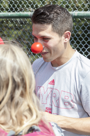 nariz roja: New York, NY, USA - May 26, 2016: New York Red Bull player Alex Muyl celebrates Red Nose Day with kids at the school yard of PS 154, Brooklyn Editorial