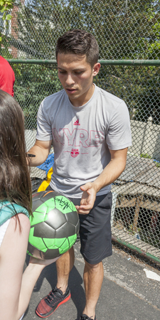 school yard: New York, NY, USA - May 26, 2016: New York Red Bull player Alex Muyl celebrates Red Nose Day with kids at the school yard of PS 154, Brooklyn Editorial