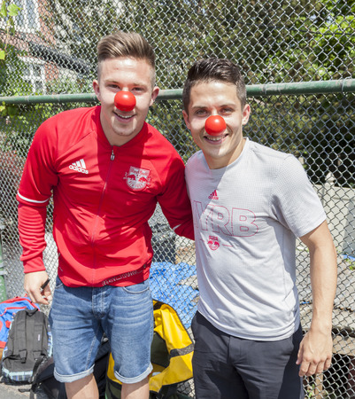ps: New York, NY, USA - May 26, 2016: New York Red Bull players Alex Muyl and Connor Lade celebrate Red Nose Day with kids at the school yard of PS 154, Brooklyn Editorial