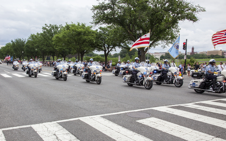 federal police: WASHINGTON D.C., USA - May 30, 2016: Police officers on the bikes participate in a Memorial Day parade on Constitution Avenue in Washington D.C. The Memorial Day is a United States federal holiday observed on the last Monday of May
