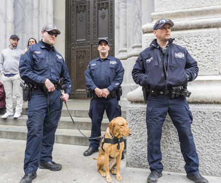 New York, NY, USA - April 1, 2018: Police officers with dog protect people at 2018 New York Easter Parade and Bonnet Festival on 5th Avenue, Manhattan near St.Patrick's Cathedral.