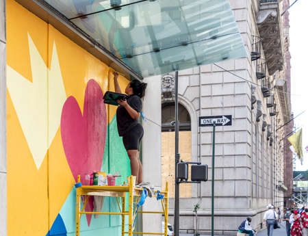New York, NY, USA - June 24, 2020: Theresa Rivera design artists paint mural 'Love NYC' on windows covered by plywood at Buchmann Tower, Midtown East, Manhattan. Building windows were boarded up with plywood in anticipation of vandalism during protest