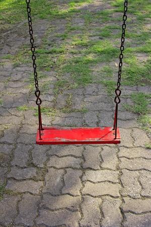 Red garden swing hanging in garden photo