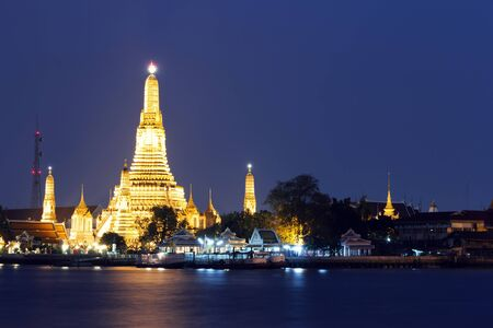 Twilight view of Wat Arun across Chao Phraya River during sunset in Bangkok, Thailand photo