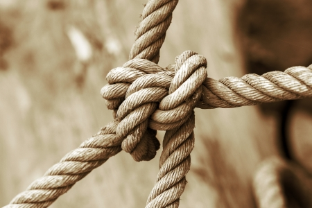 string together: strong knot tied by a rope Stock Photo